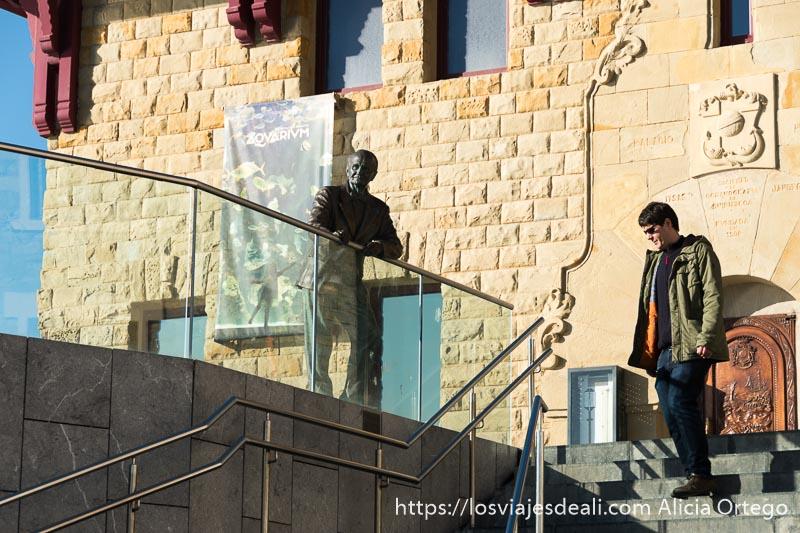 estatua del fundador del aquarium de san sebastián apoyada en una barandilla y detrás el edificio