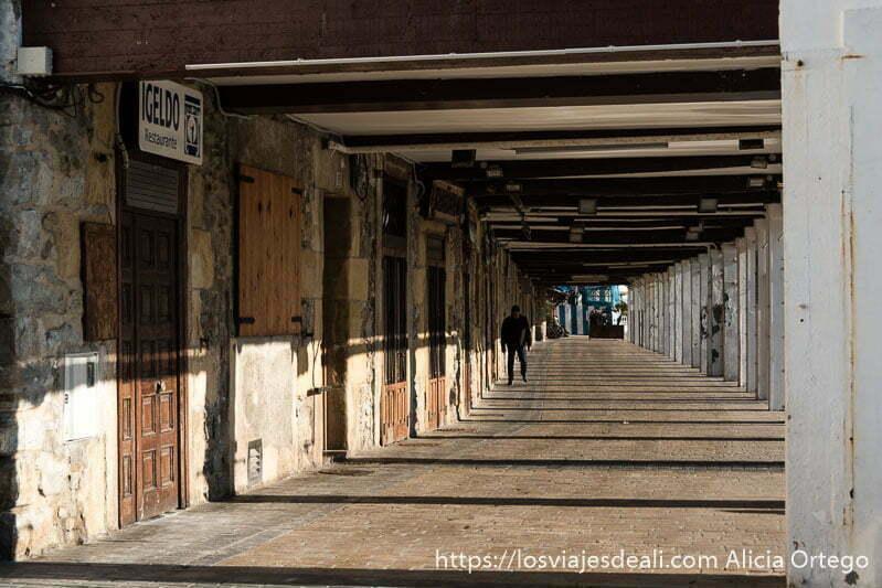 soportales llenos de restaurantes del puerto de san sebastián con el sol entrando y haciendo sombras con las columnas