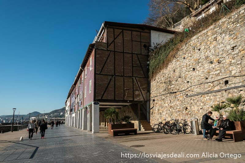 a la derecha restos de la antigua muralla de san sebastián y a continuación casas muy antiguas con ladrillos y vigas de madera oscura