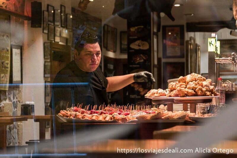 camarero preparando bandejas de pintxos en el barrio viejo de san sebastián