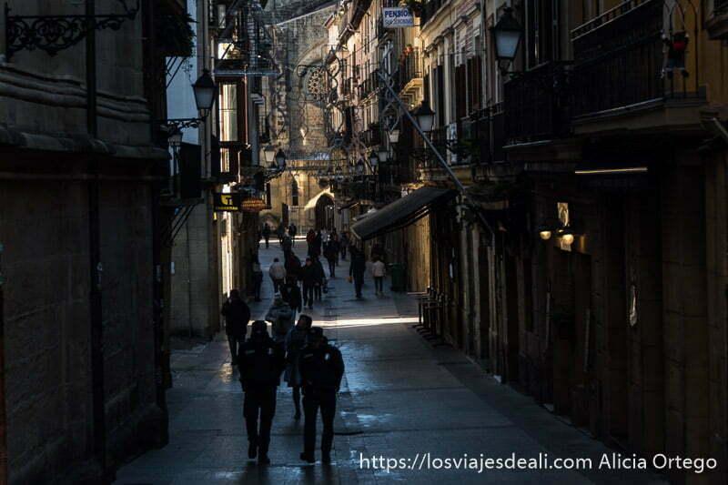 calle del barrio viejo de san sebastián con gente caminando en sombras y algunos rayos de sol iluminando partes de las fachadas
