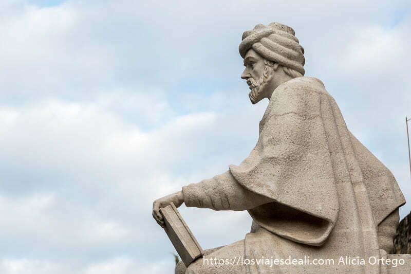 estatua de averroes de perfil con turbante y un libro en la mano apoyado en la rodilla en el centro histórico de córdoba