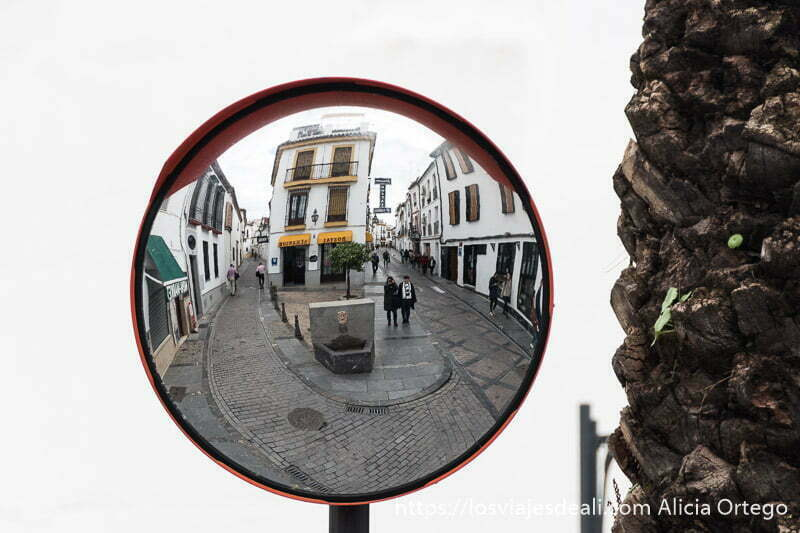 espejo de tráfico reflejando dos calles que se juntan con una fuente en el cruce