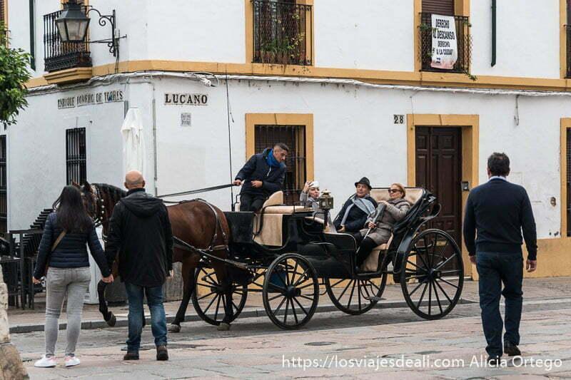 turistas haciéndose un selfie montados en carro de caballo en una calle del centro de córdoba