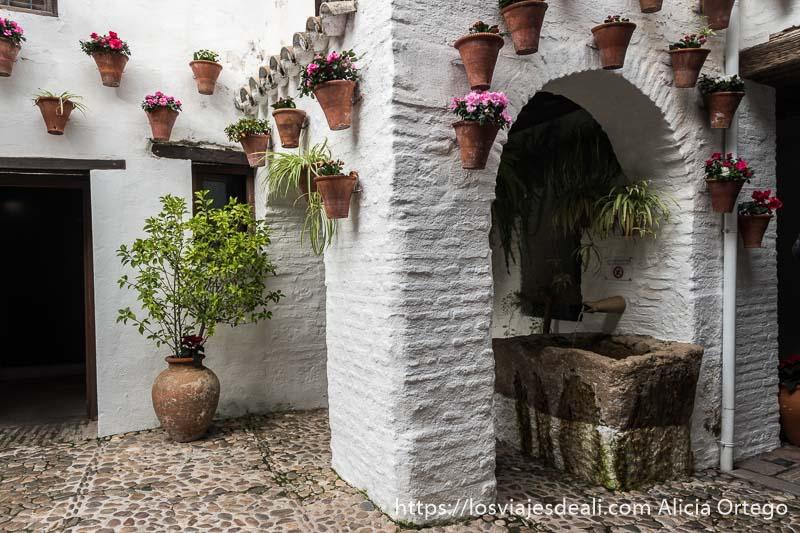 rincón con fuente de piedra y macetas de flores de la posada del potro