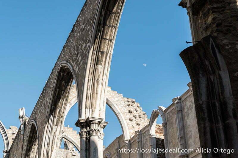 detalle de arcos góticos de piedra recortándose en el cielo azul y con la media luna en el centro de lisboa