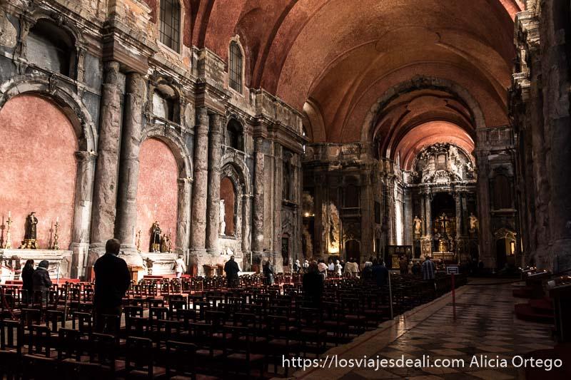 nave central de iglesia de santo domingo con columnas de piedra rotas y manchadas de hollín por el incendio y altar barroco al fondo