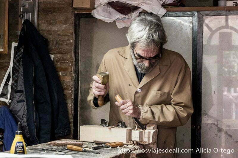 artesano de la madera trabajando en una pieza con martillo y cincel y bata marrónla judería de córdoba