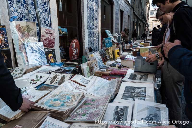 puesto de postales y mapas antiguos en una calle del chiado junto a casas con fachada de azulejos y personas ojeando libros en el centro de lisboa