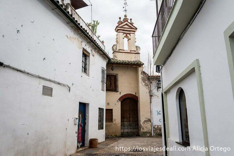callejón de casas blancas con iglesia al fondo pintada de beige en córdoba