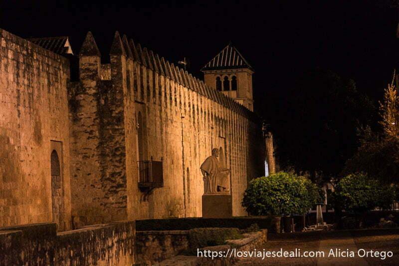 murallas con estatua de averroes de perfil y una torre al fondo por la noche en el centro histórico de córdoba