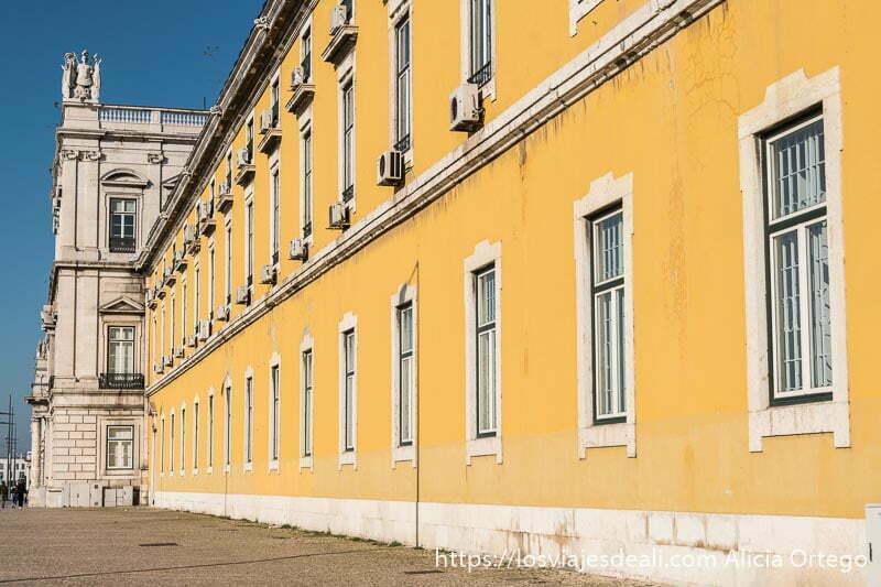 fachada de gran edificio de piedra pintado de color amarillo junto a la plaza del comercio