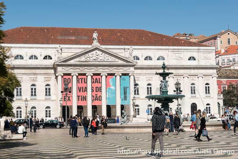 fachada del teatro nacional en la plaza de rossio con fuente de bronce y gente paseando