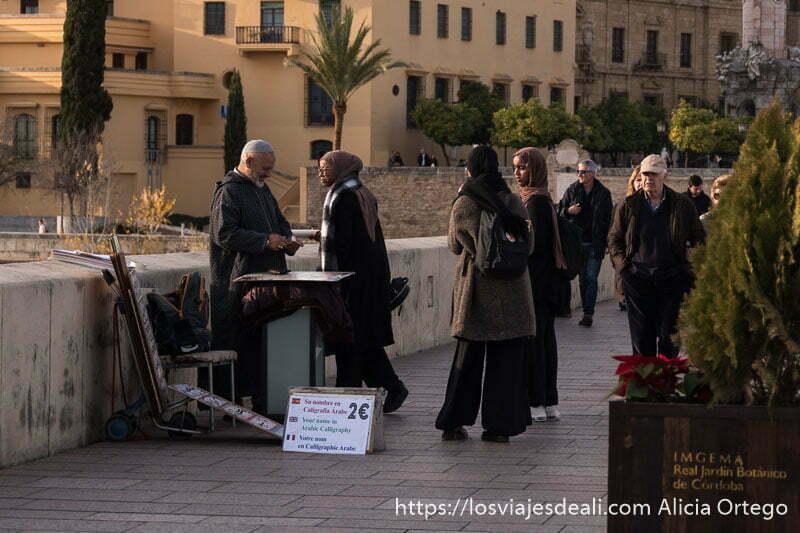 mujeres musulmanas paradas en el puente romano de córdoba con sus velos en la cabeza ante un puesto de caligrafía árabe