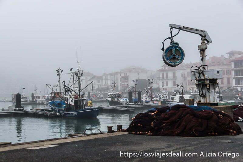 puerto de san juna de luz con grúa y montón de redes y al fondo algunos pesqueros en los muelles y mucha niebla