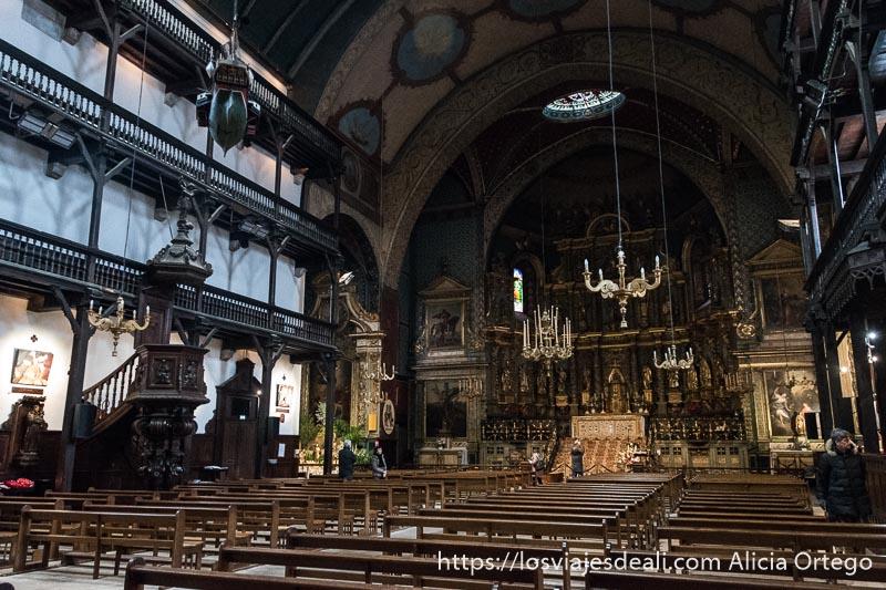 interior de la iglesia de san juan de luz con balconadas de madera y grandes lámparas tipo candelabro