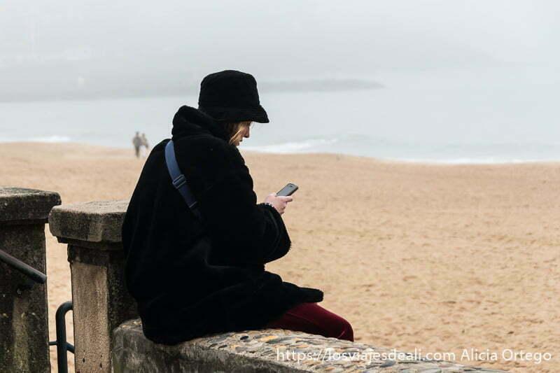 chica con abrigo negro y gorro a juego mirando el móvil sentada en murete frente a la playa de san juan de luz