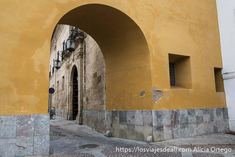 gran arco que da paso a las caballerizas con paredes pintadas de ocre en el centro histórico de córdoba