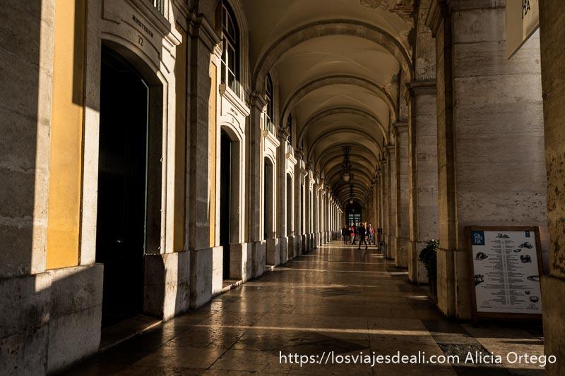 galería porticada de la plaza de comercio con el sol entrando entre las columnas en el centro de lisboa