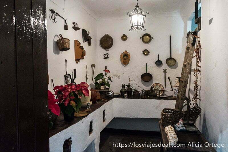 cocina antigua de uno de los patios de córdoba es una pequeña habitación con cacharros de cobre en las paredes