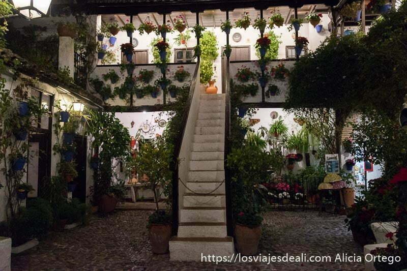patio con suelo empedrado y escalera en el centro que lleva a un balcón lleno de macetas con flores