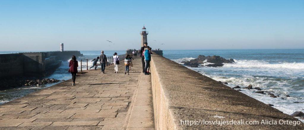 faro al fondo del espigón con el mar y personas paseando