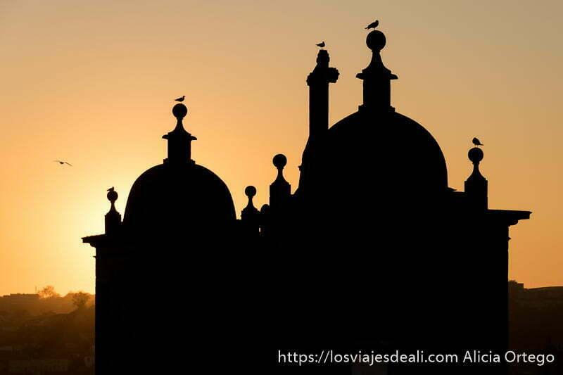 dos cúpulas y pequeñas torres terminadas en bolas con gaviotas posadas a contraluz en la puesta de sol con cielo naranja en razones para viajar a oporto