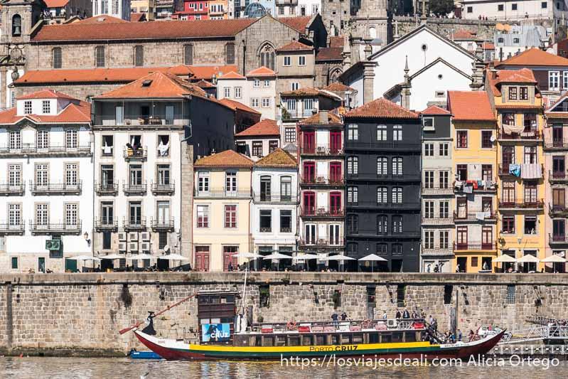 fachadas de la ribeira con distintos colores y alturas todas juntas y un barco de cruceros imitando a los antiguos amarrado en el muelle
