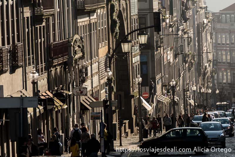 calle en cuesta con farolas y edificios iluminados por el sol con muchas sombras en oporto