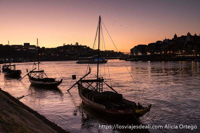 puesta de sol en el río Duero con la ciudad en las orillas y barcas de vela en primer plano en razones para viajar a oporto