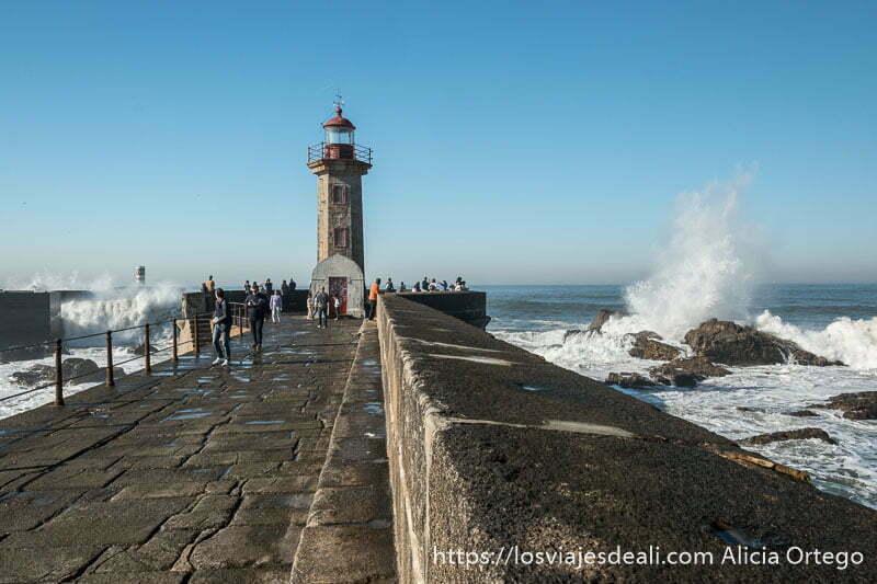 faro al fondo de paseo de piedra con olas rompiendo a los lados y el mar en foz do douro