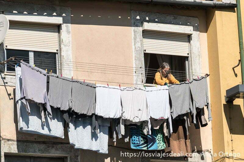 mujer mayor tendiendo la ropa en la fachada de su casa razones para viajar a oporto