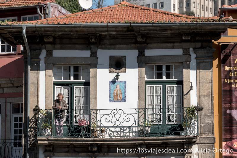casa con gran balcón en el que está asomada una mujer mayor al sol