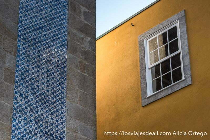 muro pintado de amarillo con ventana con cuarterones blancos se cruza con otro muro con cenefa de azulejos azules