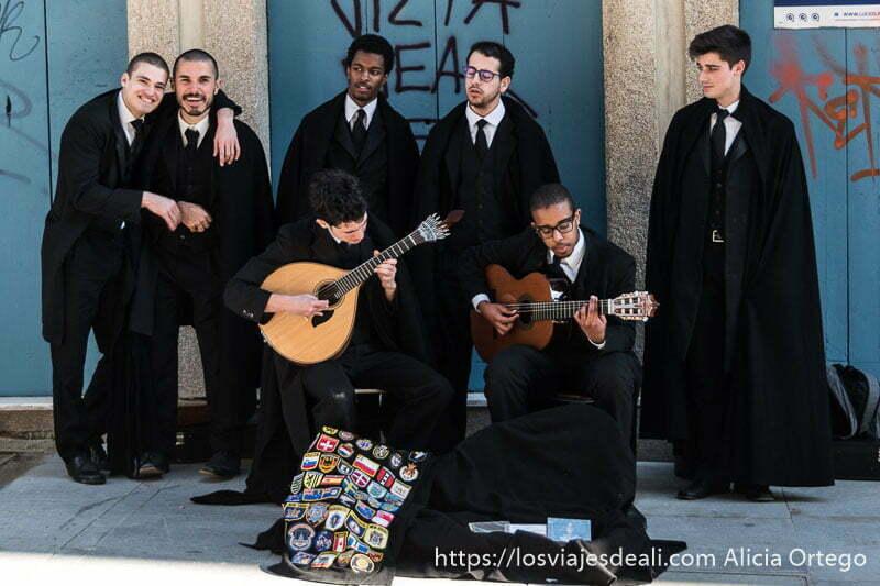 grupo de chicos vestidos de negro de la tuna, dos tocando la guitarra y otros dos mirando a la cámara riéndose razones para viajar a oporto