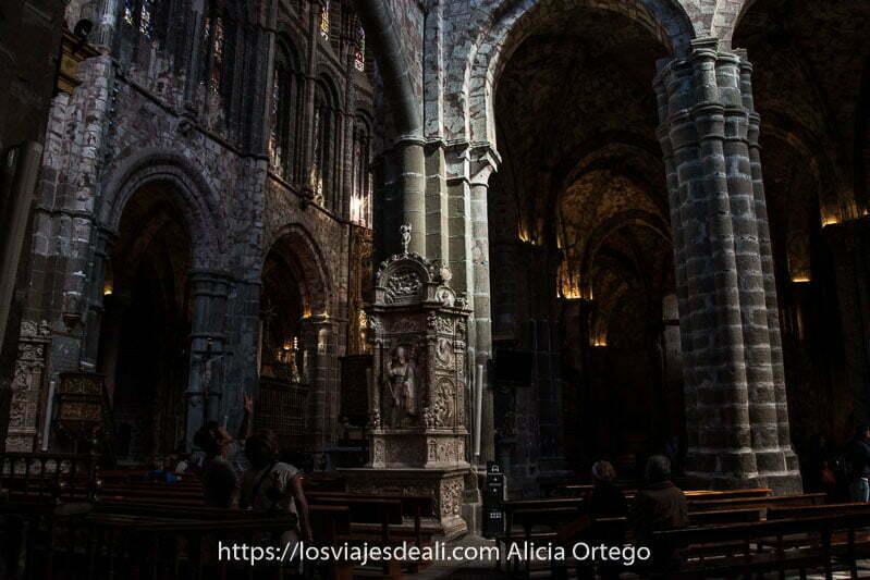 interior de la catedral de ávila con gente sentada en los bancos y otros admirando los techos