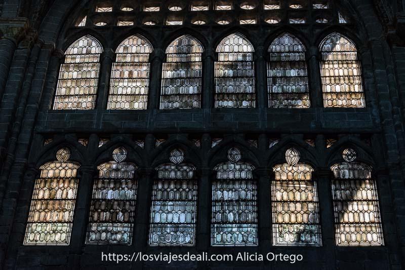 dos hileras de ventanas terminadas en arco con vidrieras por donde pasa el sol en la catedral uno de los lugares que ver en ávila