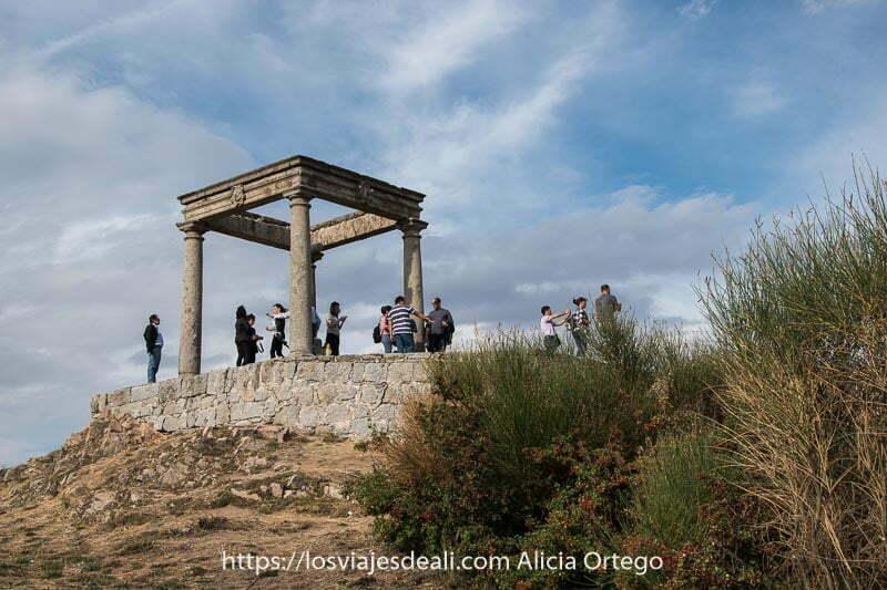 monumento de los 4 postes bajo cielo nublado con turistas haciendo fotos desde allí