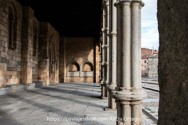 interior de la galería porticada de la basílica de san vicente con luz del sol entrando entre las columnas y estas proyectando sombra en el suelo