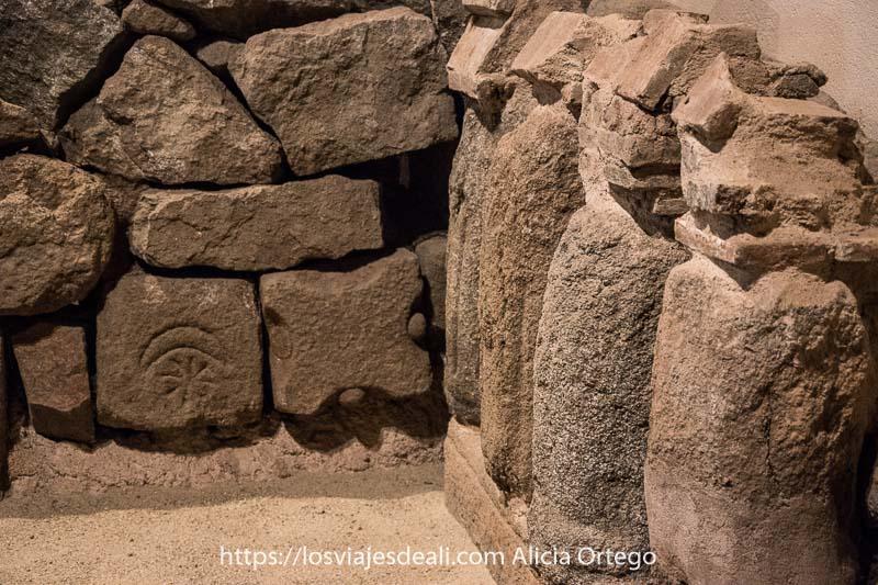 antigua tumba de piedra. Una pieza tiene un grabado del sol y la luna