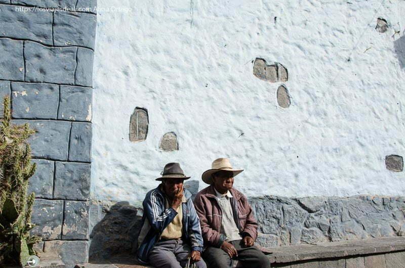 dos hombres con sombrero de ala ancha sentados en un banco de piedra contra un muro encalado en un pueblo del cañón del colca