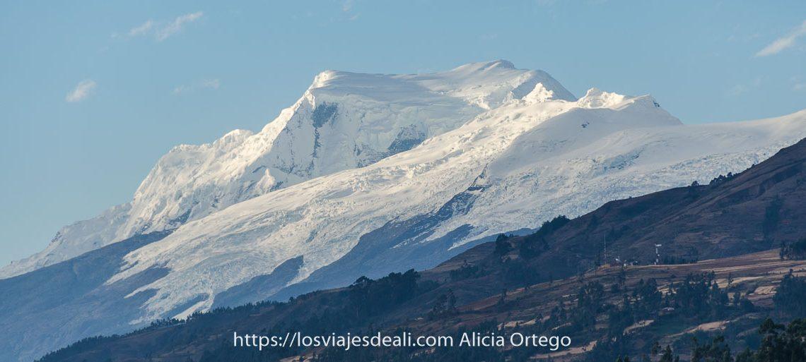 la montaña huascarán llena de nieva con otros picos nevados alrededor es uno de los lugares maravillosos de perú