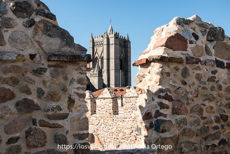 torre de la catedral vista entre las almenas de la muralla, dos lugares que ver en ávila