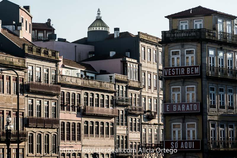 """casas de oporto llenas de ventanas y en una fachada cartel que dice """"vestir bem e barato solo aquí"""""""