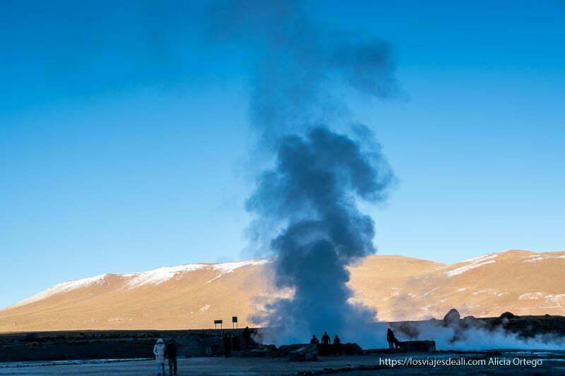 amanecer en los geyseres del tatio con gran fumarola en el centro y montañas al fondo