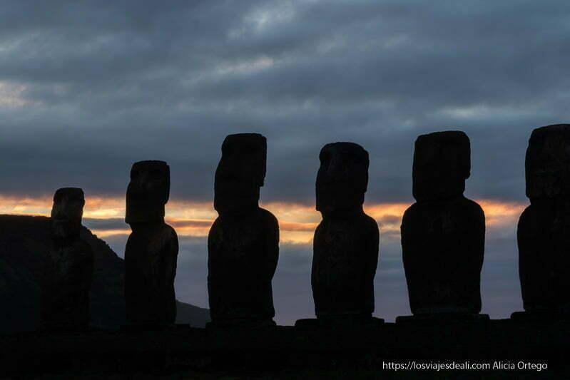 moais en contraste no nubes de tormenta y línea rojiza del amanecer en tongariki