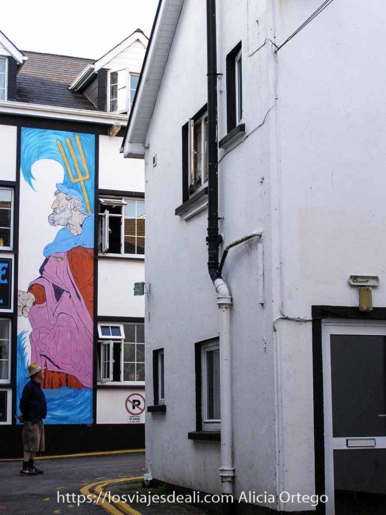mural en la fachada de una casa de killarney representando a Neptuno y un señor con sombrero de ala ancha parado junto a él
