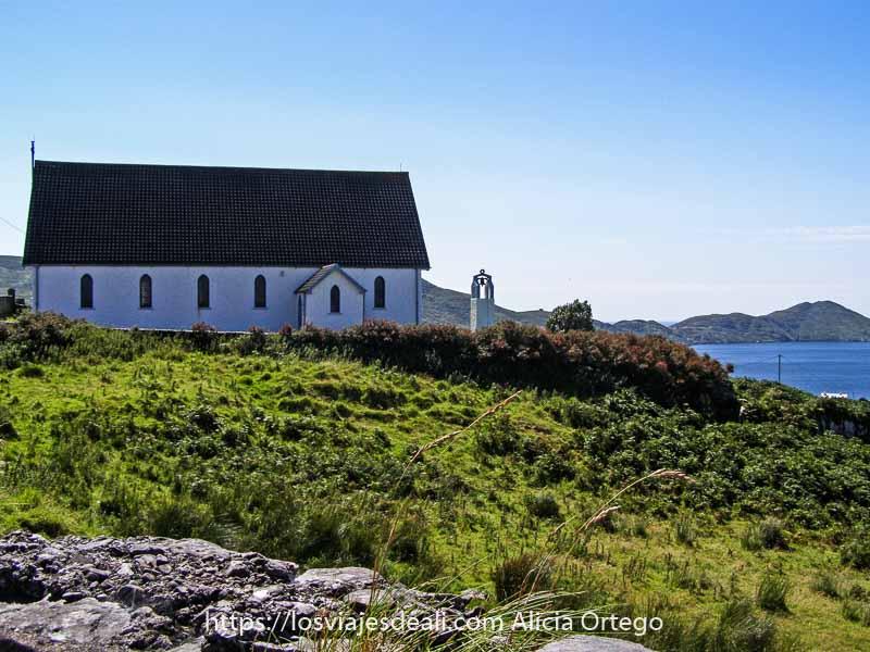 iglesia pintada de blanco con gran tejado de pizarra al borde del mar, rodeada de verde, en caherdaniel