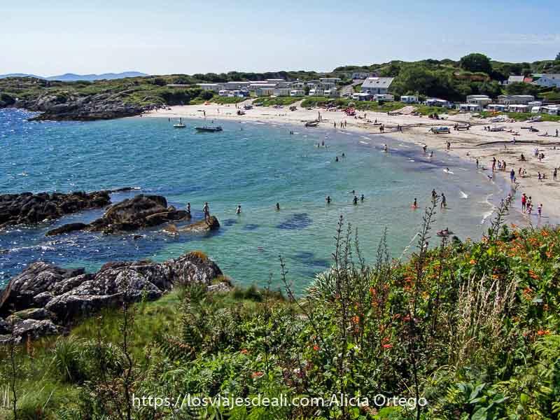 playa de arena blanca y aguas turquesas resguardada por rocas con gente bañándose y pueblo alrededor en caherdaniel