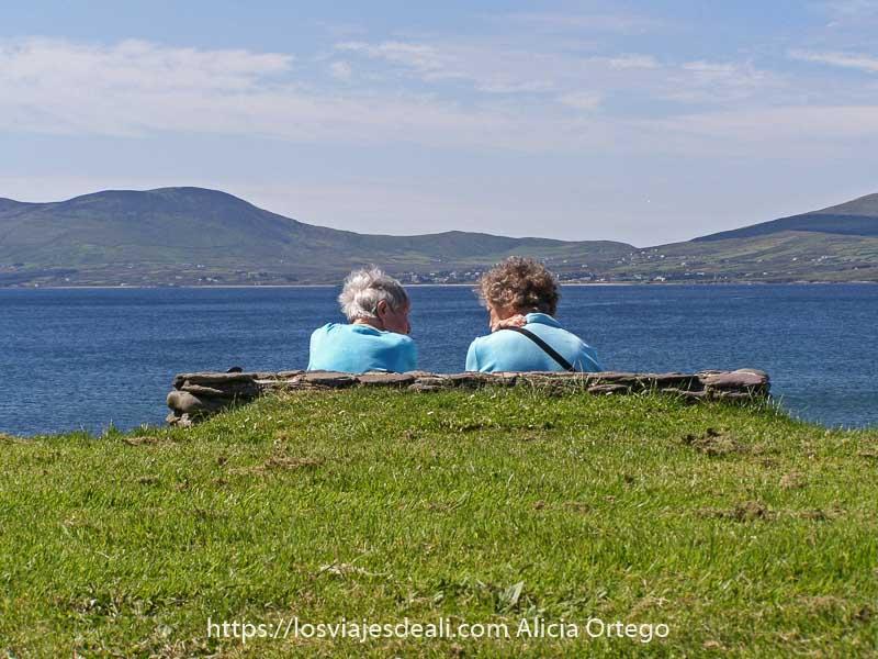 dos mujeres mayores sentadas en un banco de espaldas a la cámara hablando con el mismo jersey azul claro y ante ellas el mar y montañas al fondo